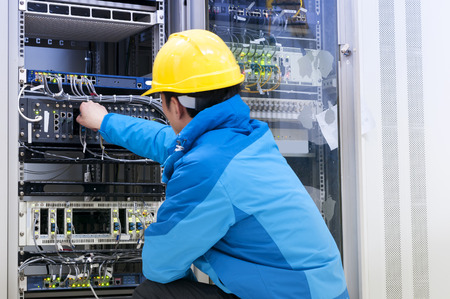 Man connecting network cables to switches Zdjęcie Seryjne
