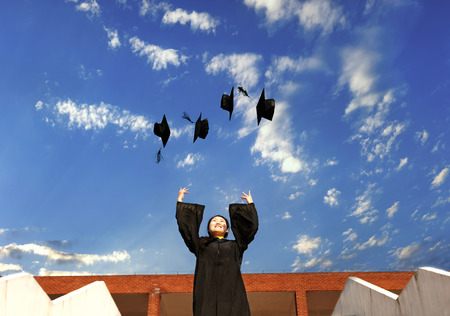 pretty graduate throwing graduation hats in the air. photo