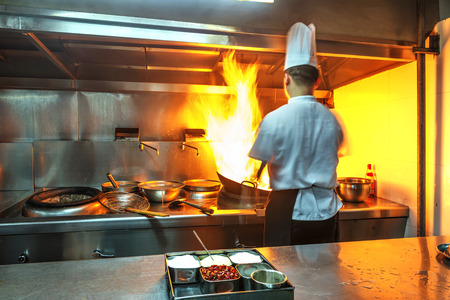 keuken restaurant: Chef in restaurant kitchen at stove with pan, doing flambe on food