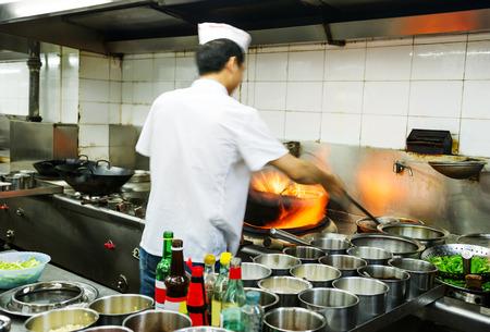 keuken restaurant: Chef-kok in restaurant keuken aan fornuis met pan, doe flambe op voedsel