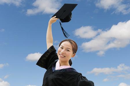 GRADUADO: Graduado vistiendo traje de graduación femenina hermosa Foto de archivo