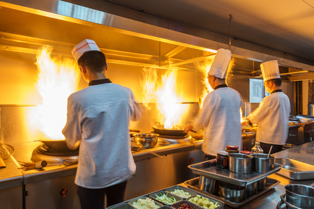 chef: Chef in restaurant kitchen at stove with pan, doing flambe on food