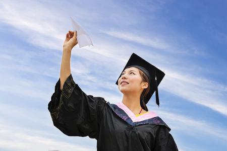 toga y birrete: Graduado de la hembra hermosa que desgasta el vestido de la graduación, lanzando avión