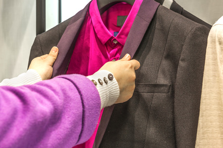 blue grey coat:  woman choosing man suit jackets on hangers Stock Photo