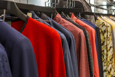 ropa deportiva: A row of colorful row t-shirts hanging on hangers Foto de archivo