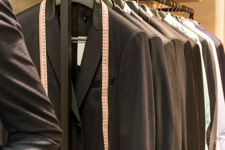 blue grey coat: Row of men suit jackets on hangers