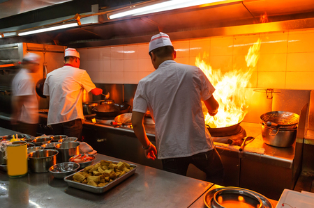 restaurant industry: Crowded kitchen, a narrow aisle, working chef.