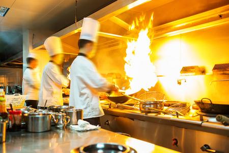 jefe de cocina: Chef en el restaurante de cocina en cocina con la cacerola, haciendo flambeado en alimentos