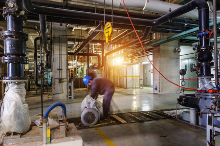 mantenimiento: ingeniero de mantenimiento que controla datos técnicos del equipo del sistema de calefacción en una sala de calderas