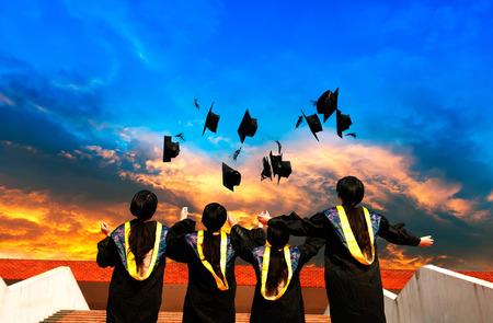 graduating seniors: pretty graduates throwing graduation hats in the air. Stock Photo