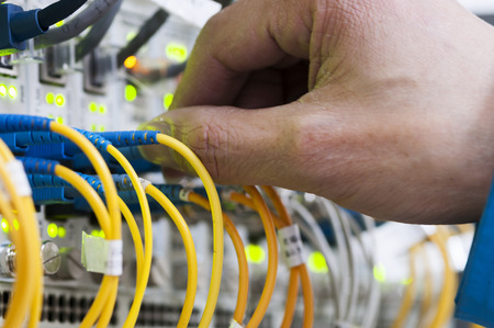 linkage: Man connecting network cables to switches Stock Photo