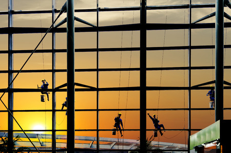 Washers wash the windows of modern skyscraper Stock Photo