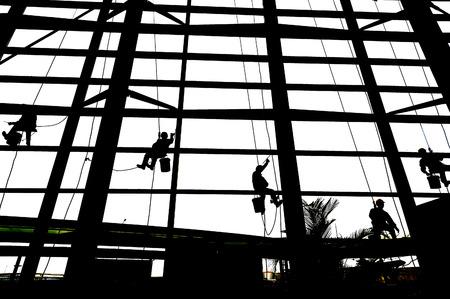Washers wash the windows of modern skyscraper 版權商用圖片