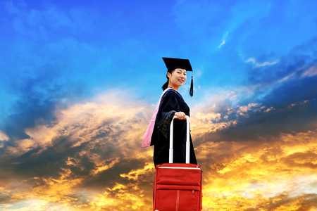 academic robe: Beautiful female graduate wearing a graduation gown holding red luggage