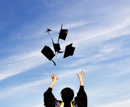 graduating seniors: graduate throwing graduation hats in the air.