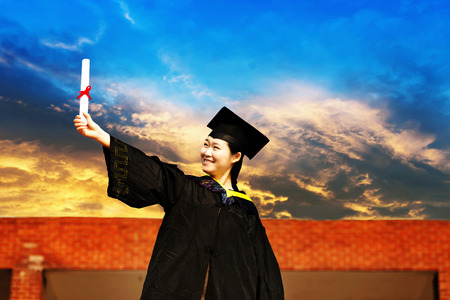 Beautiful female graduate wearing a graduation gown Stock Photo