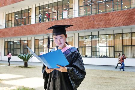 Beautiful female graduate wearing a graduation gown,reading