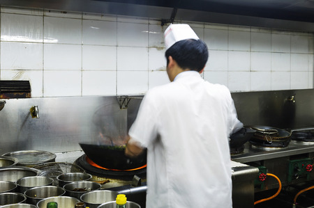 hotel staff: Crowded kitchen, a narrow aisle, working chef.