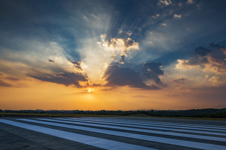 Runway, airstrip in the airport terminal with marking in sunset background. Stock Photo