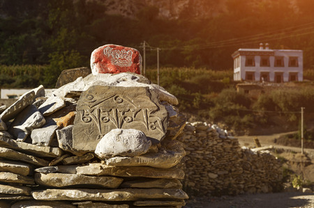 The stone carved the word prayer that translates as Om Mani Padme Hum