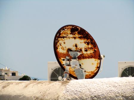 damaged roof: rusted satellite dish Stock Photo