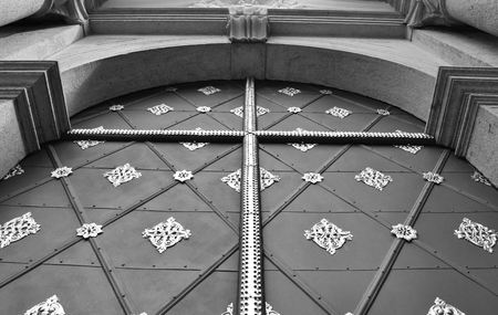 The decorated and ancient main door of the Basilica of the Assumption in the Strahov Monastery in Prague, in Czech Republic. Black and white.