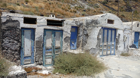 Abandoned buildings at port of Therasia, little island near Santorini, Greece