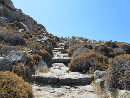 ortigia: Ruins of a stairs on a hill with tourists in Delos island, Cyclades archipelago, Greece.