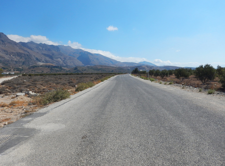 empedrado: A tarmac road in a flat landscape with mountains in background