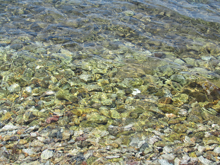 Transparent green sea with pebbles on the bottom Stock Photo