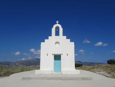 An isolated white Greek Orthodox Church with turquoise door in Antiparos island, Cyclades. Blue sky and little clouds in the background. Stock Photo