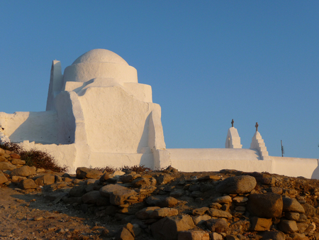 A white Greek Orthodox Church in Cyclades island at sunset