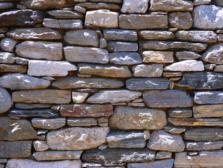 A rough stone wall with sun. Suitable to be used like a background. Stock Photo