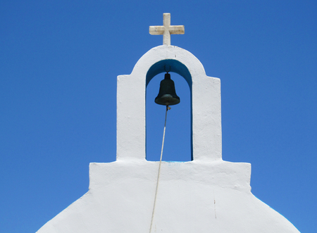 A white bell tower with cross in a Greek Orthodox Church. Blue sky in the background.