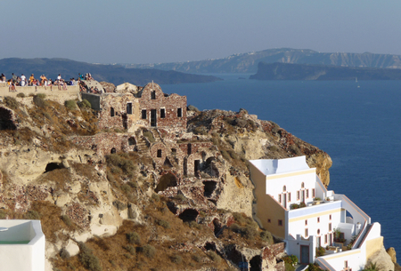 Tourists look sunset from ancient ruins at Oia village, Santorini, Greece.  Editorial