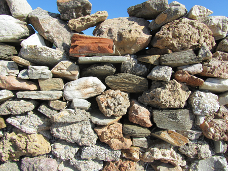 A rough colored wall stone with blue sky. Suitable to be used like a background.