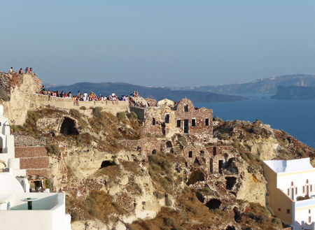 Tourists look sunset from ancient ruins at Oia village, Santorini, Greece.  新聞圖片