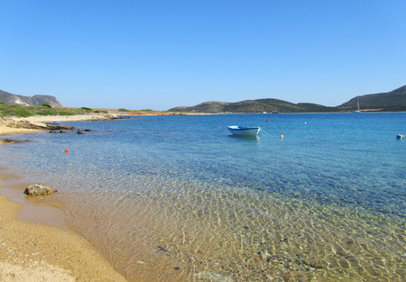 A sandy beach in Antiparos with limpid turquoise sea, a boat and a view of Despotiko island on the background. In Cyclades, Greece.