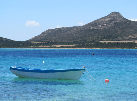 The coast of Antiparos with limpid turquoise sea, a boat and a view of Despotiko island on the background. In Cyclades, Greece