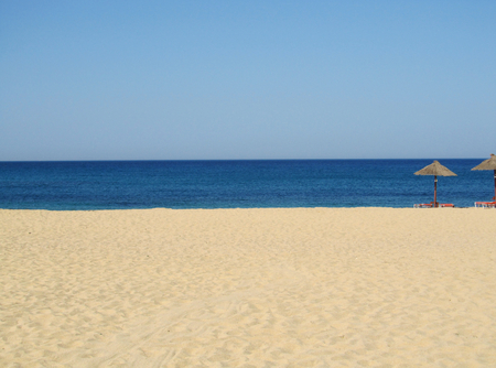 Summer stripes: sandy beach, blue sea, limpid sky. Stock Photo