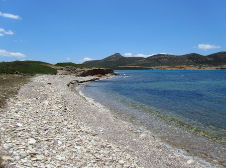 A rocky white beach in Antiparos with Despotiko island in the background, Cyclades, Greece