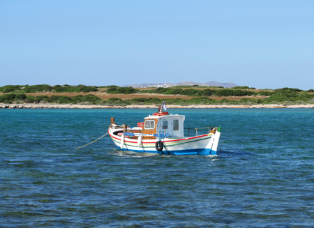 A traditional colored little boat on a blue sea with a flat wild land in the background in a sunny day.
