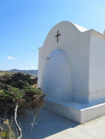 A white Greek Orthodox Church near a tree in Antiparos, Cyclades island. Stock Photo