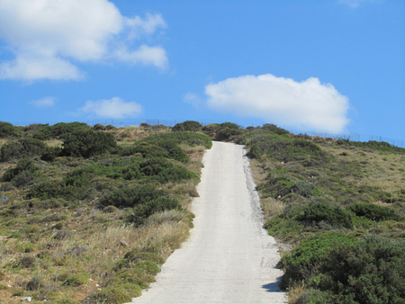 A dirty road in a wild landscape with nobody; blue sky and white clouds in the background. Greece.