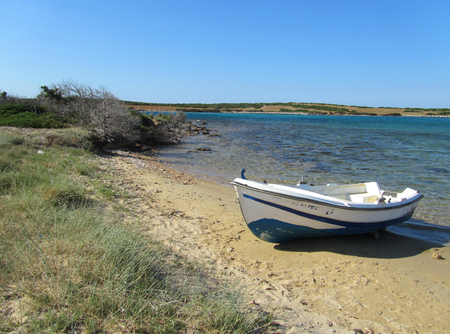 A white little boat on a sandy beach near a limpid sea with a flat wild land in the background in a sunny day. Greece. Stock Photo