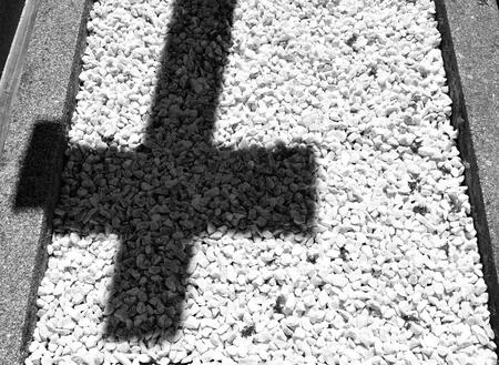 The shadow of a cross on a floor of little white stones in a cemetery: concept of sorrow and grief. Black and white. Stock Photo - 94116233