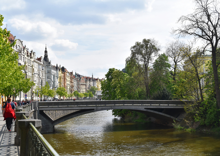 A little bridge on a river with colorful buildings in Prague city center, in Czech Republic