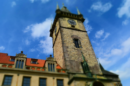 The clock tower of Old Town Hall in Prague in Czech Republic, with blue sky and white clouds in the background. Tilt-shift effect applied. Stock Photo