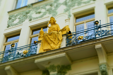 A golden statue of a young woman in a terrace of an ancient white palace in Prague in Czech Republic. Tilt-shift effect applied.