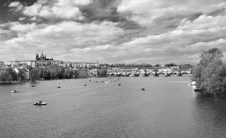 View of the Charles Bridge and the river Vltava with a lot of pedal boats, in Prague in Czech Republic. Black and white.